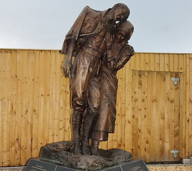 A bronze war memorial showing a woman supporting an injured soldier.